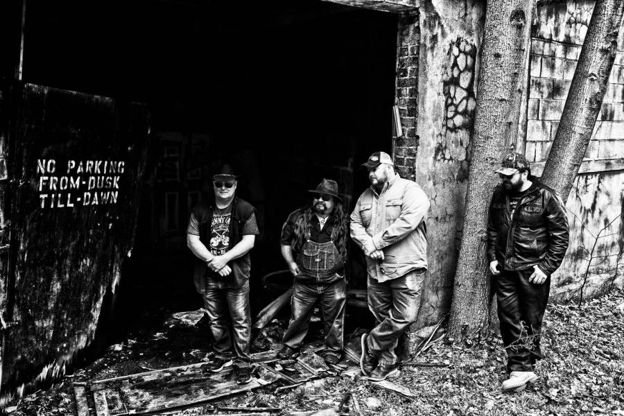 Warren Butler band standing outside of an old building